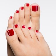 Closeup photo of a beautiful female feet with red pedicure isolated on white