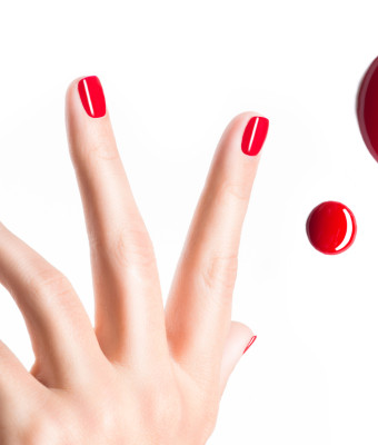 Beautiful female hands with red manicure and  drops of nail polish